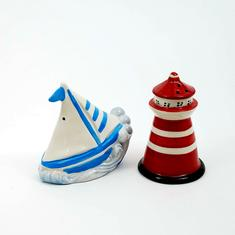 White with blue stripe sailboat and red lighthouse salt and pepper shaker set from Premier Homegoods site